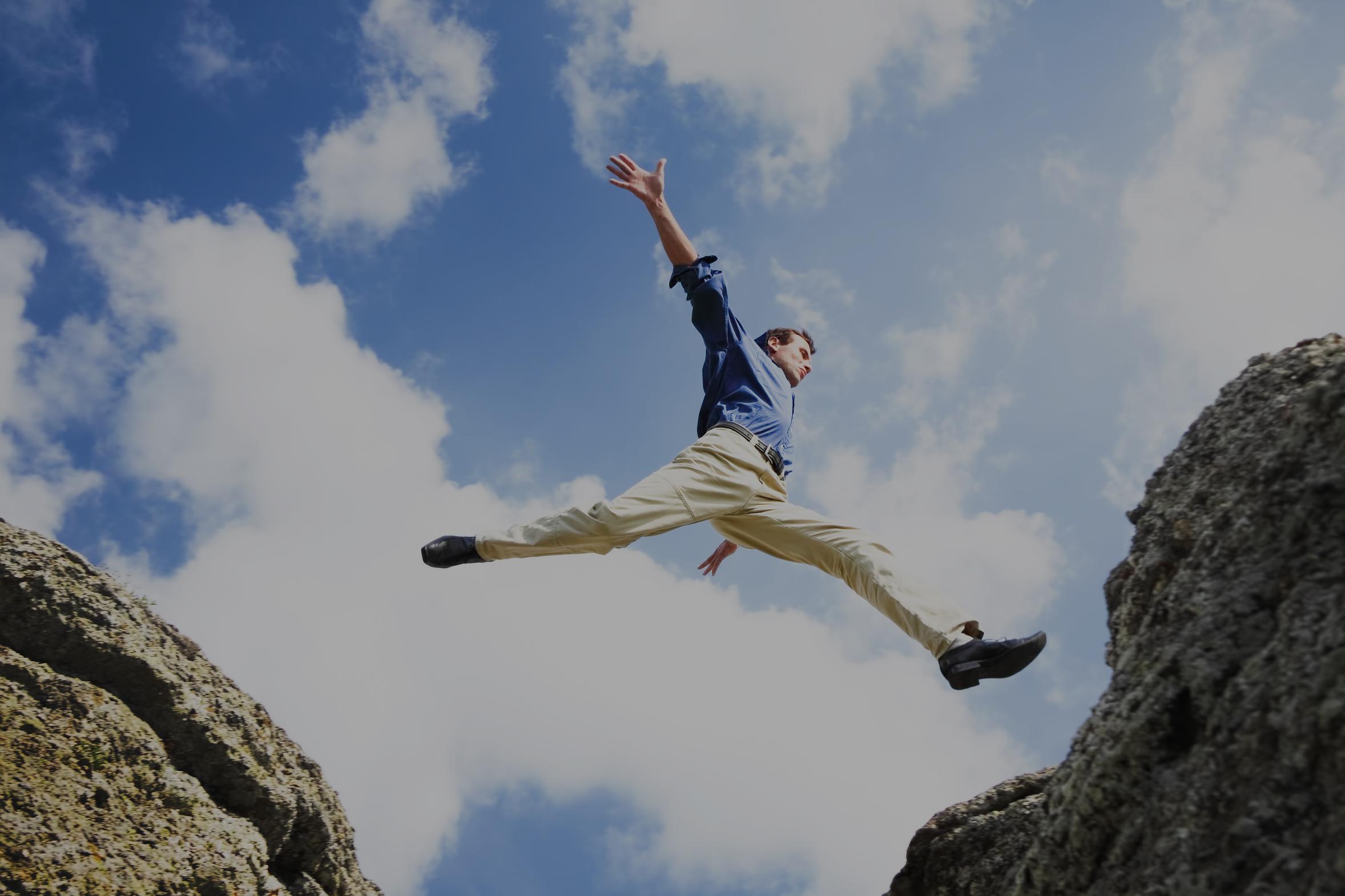 uomo d'affari felice salta da una montagna sotto un cielo azzurro e supera l'ostacolo del vuoto
